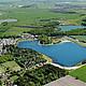 Ein türkisblauer See umgeben von Wald und Wiesen, so sieht der Ferienpark von oben aus.
