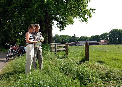 Radlerpaar mit Radkarte vor Weide